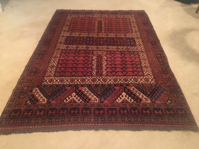 hand knotted tribal rug rust background
